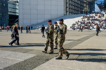 where to eat: Paris, France, October 27, 2014 - Soldiers patrol La Grande Arche where government and business employees as well as tourists eat lunch on its steps. La Defense is a major commercial center in the city.