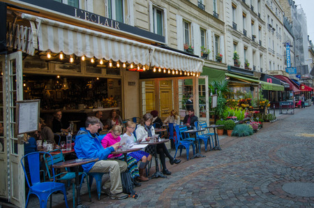 Paris, France, October 7, 2014 - A family checks out the lunch menu at an outdoor caf? in the charming Rue Cler neighborhood.