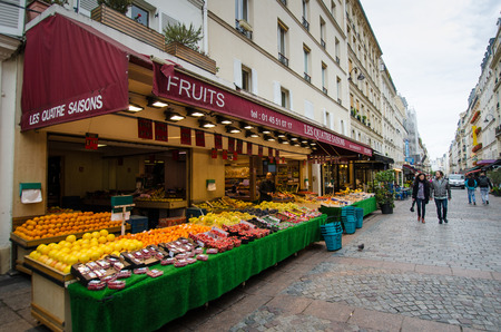 rue: Paris, France. October 7, 2014 - A couple walks by an outdoor market selling fruits and vegetables in the charming neighborhood of Rue Cler.