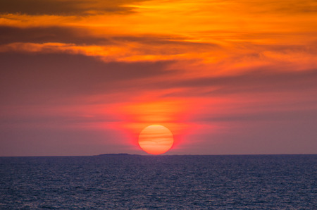 A fiery red sun sets on the Baltic Sea as a cruise ship leaves Helsinki, Finland.