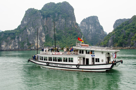halong: Halong Bay, Vietnam, February 12, 2015 - A boat carrying tourists cruises among hundreds a small islands in Halong Bay