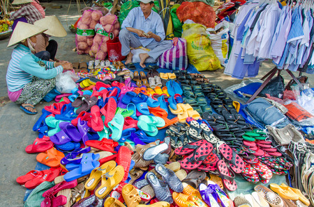 chan: Chan May, Vietnam, February 10, 2015 - Two women examine the colorful sandals and shoes for sale at an outdoor market. Editorial