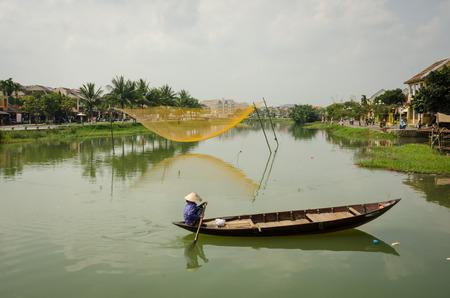 bn: Hoi An, Vietnam, 10 de febrero 2015 - mujer vietnamita bate un barco tradicional en el Thu B n River?. Una red para atrapar los peces se suspende en los postes en el medio del r�o.