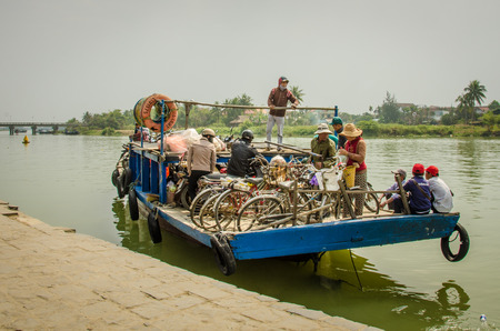 bn: Hoi An, Vietnam, February 10, 2015 - A crowded ferry transports people and their bicycles along the Thu B?n River. Hoi An is an UNESCO World Heritage Site.