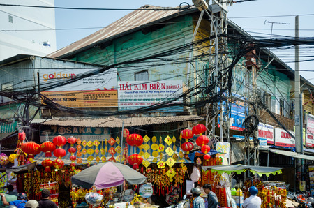 oblivious: Saigon, Vietnam, February 7, 2015 ? People on the street are oblivious to the dangers of the tangled mess of power and telecommunications cables overhead.  Although the cables pose a threat of a major fire, efforts to bury them underground have failed. Editorial