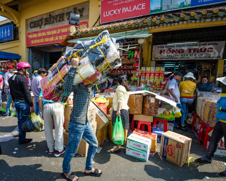 bargains: Saigon, Vietnam, February 7, 2015 ? Man carries a heavy load of goods on his back in Chinatown. Cholon, the Chinese market, is crowded, chaotic and colorful with plenty of bargains.