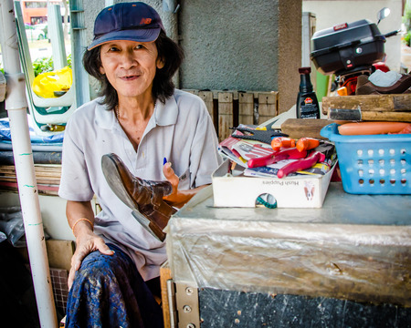 earns: Singapore City Singapore February 1 2015  Old woman earns a living by shining shoes at an outdoor stand on a main street. Singapore may be one of the wealthiest and most developed countries in the world but poverty remains a worrying problem.