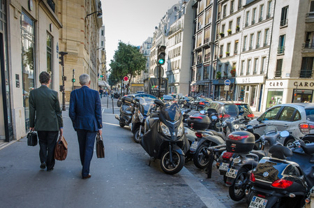 rue: Paris, France, October 3, 2014 - Two male executives carrying brief cases walk along Rue de Turbigo in the Marais district with motorcycles lining the street. Editorial