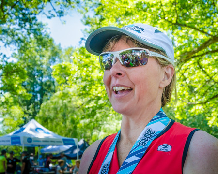 competitor: Victoria, Canada, June 14, 2015 - Happy female competitor greets her family after completing the grueling Ironman race at Elk Lake. Her supporters are reflected in her sunglasses.