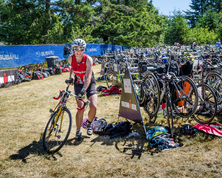 ironman: Victoria, Canada, June 14, 2015 - Female competitor enters the bike pound after finishing her ride before beginning her run during the Ironman Triathlon 70.3 competition held at Elk Lake in British Columbia.