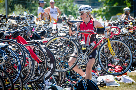 ironman: Victoria, Canada, June 14, 2015 - Female competitor places bike back in her rack during the gruelling Ironman Triathlon 70.3 competition held at Elk Lake in British Columbia.