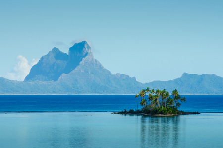 south pacific ocean: View of an island with palm trees in the South Pacific Ocean with Bora Bora in the distance.