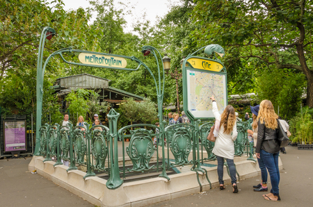 retained: Paris, France, September 8, 2015  Two girls examine map outside the Cite Metro station which is one of the few that have retained its original Art Nouveau sculpted entrance designed by architect Hector Guimard.