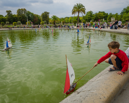 plays: Paris, France, August 18, 2015 - A boy plays with a sailboat in the pond at the Luxembourg Gardens on a summer afternoon.