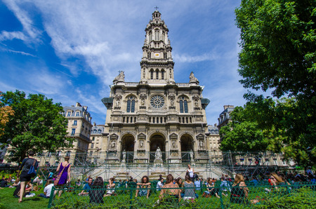 lunch hour: Paris, France, August 10, 2015 - People are relaxing and even having a nap on the bench during their lunch hour at Sainte-Trinite Square where the parish church is under renovation. Editorial
