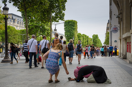 begs: Paris, France, August 8, 2015 - A tourist places coins in the cup of a woman kneeling as she begs for alms on the sidewalk of the Champs-Elysees known for its luxury shops. Crowds pass by without paying attention to the kneeling woman.