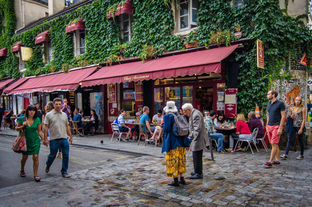 marianne: Paris, France, August 16, 2015 - An older couple walk along Rue Hospitalires St. Gervais in front of Chez Marianne, a popular restaurant in the historic district of Marais.