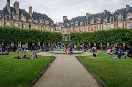 historic place: Paris, France, August 16, 2015 - People are relaxing on the lawns and in front of the fountain of the historic Place des Vosges, inaugurated as Place Royale in 1612, the oldest square in the city.