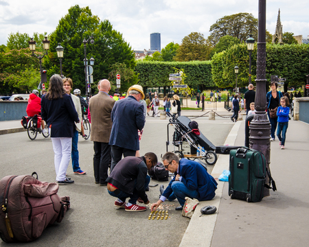 cite: Paris, France, August 15, 2015 - People watch as musicians count their coins on the street after performing on Pont Saint Louis, the bridge connecting two small islands, Cite and Saint Louis.