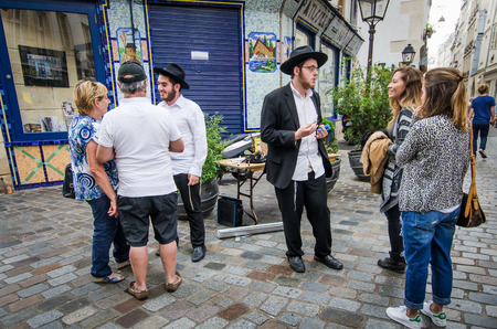 reach out: Paris, France, August 16, 2015 - Orthodox Jewish young men reach out to tourists discussing their religious beliefs in the historic district of Marais. Editorial