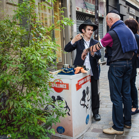 god box: Paris, France, August 16, 2015 - Orthodox Jewish young man wraps the arm of a tourist in the Marais district with leather straps, holding two small black boxes called Tefillin, which contain verses from the Torah, to be worn on the head during morning pra