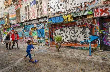 rue: Paris, France, September 12, 2015 - Family passes by abandoned storefronts on Rue Denoyez, which has been taken over by street artists bringing a kaleidoscope of ever changing murals on its walls. Editorial