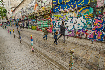 Paris, France, September 12, 2015 - Family passes by abandoned storefronts on Rue Denoyez, which has been taken over by street artists bringing a kaleidoscope of ever changing murals on its walls. Editorial
