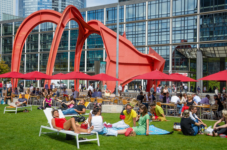 lunch hour: Paris, France, August 11, 2015 - Employees of government and commercial offices at La Defense take a break during their lunch hour on one of the green spaces in the complex with the Red Spider sculpture in the background.
