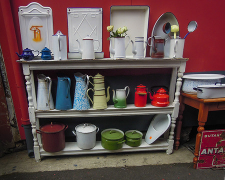 antiques: Paris, France, September 5, 2015 - Colorful Enamel pots for sale at Puces St. Ouen, a sprawling flea market with a hodgepodge of more than 2,000 vendors selling a wide range of goods including antiques. Editorial