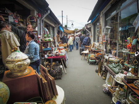 check out: Paris, France, September 5, 2015 - People check out goods at Puces St. Ouen, a sprawling flea market with a hodgepodge of more than 2,000 vendors selling a wide range of goods including antiques. Editorial