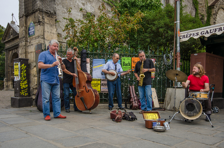 entertain: Paris, France, August 10, 2015 - Street musicians entertain passers-by with a selection of instruments playing Jazz in Place Saint-Germain des-Pres. Editorial