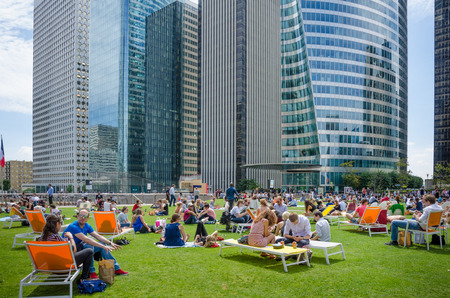 lunch hour: Paris, France, August 11, 2015 - Employees of government and commercial offices at La Defense take a break during their lunch hour on one of the green spaces in the complex with modern office buildings in the background. Editorial