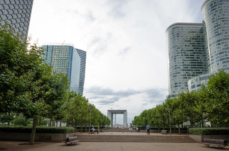 la defense: Paris, France, August 11, 2015 - People walk along the pedestrian walkway, the central esplanade at the vast government and commercial complex at La Defense with La Grande Arche in the distance. Editorial