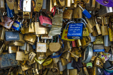 ile de la cite: Paris, France, August 10, 2015 - Close-up of some of the hundreds of locks left by lovers with their names adorn the side of Pont de lArcheveche behind Notre-Dame Cathedral connecting Ile de la Cite with the Left Bank.