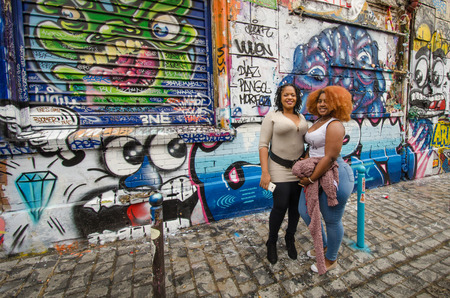 threatened: Paris, France, September 12, 2015 - Both locals and tourists pose for photos in front of the dazzling street art on Rue Denoyez where colorful graffiti covers the walls of the small pedestrian street. The street art is threatened as the city has recently  Editorial
