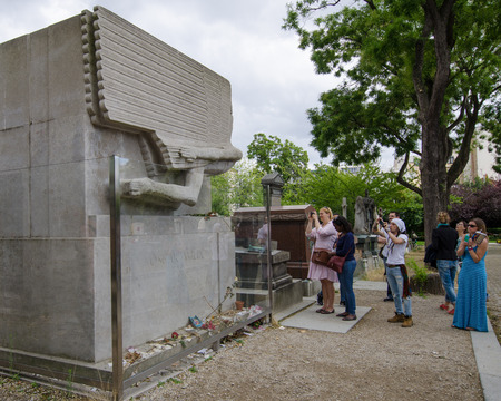 outcast: Paris, France, August 16, 2015 - Female fans take photos at the tomb of Oscar Wilde, famous Irish playwright who is mourned by outcast men. This historic cemetery is one of the most popular tourist attractions crammed with 70,000 grave sites.