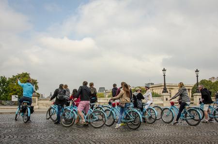 ile de la cite: Paris, France September 8, 2015 - Bicycle tour group of tourists gather on Pont Neuf over the Seine after touring Ile de la Cite.