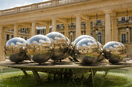 bury: Paris, France, September 7, 2015 - Silver balls in the fountain designed by Belgian sculpture Pol Bury reflect the Royal Palace courtyard on a sunny, summer day. Editorial