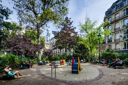 lunch hour: Paris, France, August 26, 2015 - Parisians who work in the neighborhood relax during lunch hour on a sunny summer day at a local playground. Editorial