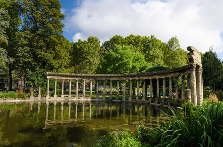 roman pillar: Paris, France, August 28, 2015 - Parc Monceau, created as a public park in 1776, contains numerous statues and reconstructions including a Roman colonnade beside a pond.