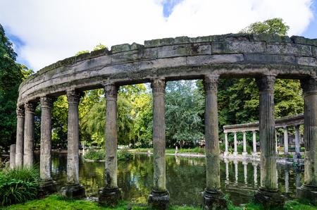 roman pillar: Paris, France, August 28, 2015 - Parc Monceau, created as a public park in 1776, contains numerous statues and reconstructions including a Roman colonnade beside a pond.