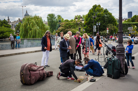 cite: Paris, France, August 15, 2015 - People watch as musicians count their coins on the street after performing on Pont Saint-Louis, the bridge connecting two small islands, Cite and Saint-Louis.