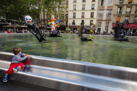 igor: PARIS - FRANCE, SEPTEMBER 3, 2015: Boy gazes at the whimsical colorful sculptures at the Stravinsky Fountain which represent the music of Russian composer Igor Stravinskys The Rite of Spring.