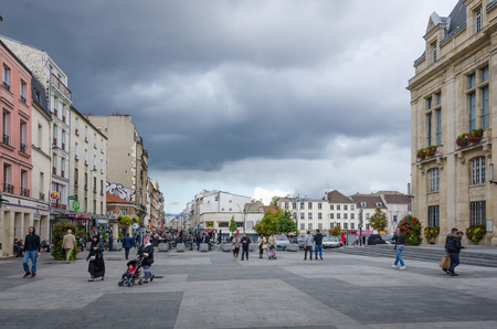 rue: SAINT-DENIS - FRANCE, SEPTEMBER 14, 2015: People are walking in front of the City Hall of Saint-Denis, which overlooks Place Victor Hugo with Rue de la Republique in the distance. Saint-Denis is a suburb of the French capital.