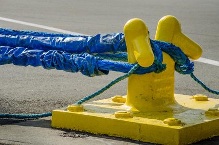 mooring bollard: Heavy blue ropes of an ocean-going ship wrap around a yellow mooring bollard on a city pier in the harbor. Stock Photo