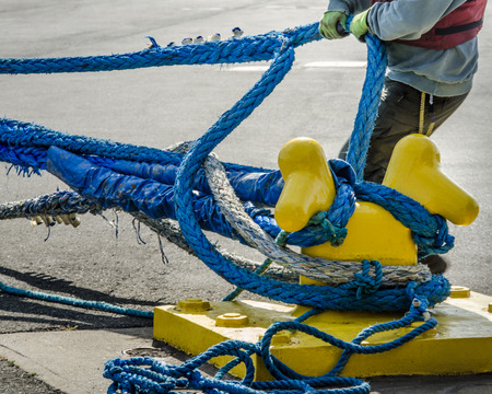 mooring bollard: Dock worker pulls on heavy blue ropes of an ocean-going passenger ship are wrapped around a yellow mooring bollard on a city pier in the harbor.