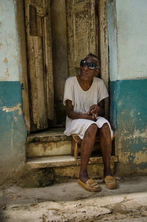 vieja: HAVANA - CUBA JUNE 19, 2016: A blind old woman wearing dark glasses sits on the stoop of her home, one of thousands of deteriorating and decaying buildings in La Habana Vieja. Editorial