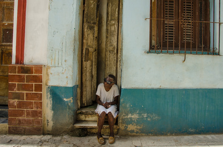 habana: HAVANA - CUBA JUNE 19, 2016: A blind old woman wearing dark glasses sits on the stoop of her home, one of thousands of deteriorating and decaying buildings in La Habana Vieja. Editorial