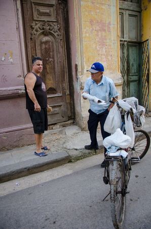 vieja: HAVANA - CUBA JUNE 19, 2016: An old man on a bicycle delivers newspapers to a resident of one of thousands of deteriorating and decaying buildings in La Habana Vieja.