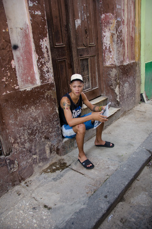stoop: HAVANA - CUBA JUNE 19, 2016: A young man with tattoos and holding a newspaper sits on the stoop of his home, one of thousands of deteriorating and decaying buildings in La Habana Vieja.